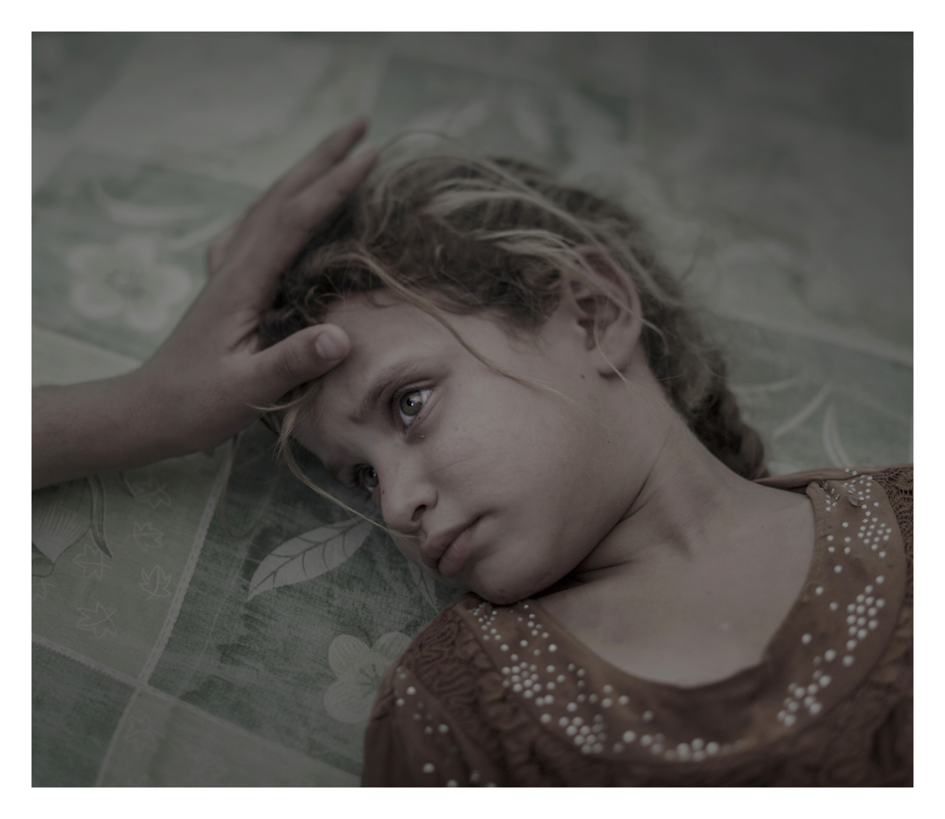 Maha, 5år. DEBAGA, IRAK.  Maha, 5 och hennes familj flydde från byn Hawiga utanför Mosul för sju dagar sedan. Skräcken för IS och bristen på mat gjorde att de var tvungna att lämna sitt hem berättar hennes mamma. Nu ligger Maha på en smutsig madrass i det överfulla transit-tältet i flyktinglägret Debaga.  Jag drömmer inte och jag är inte rädd för någonting längre säger Maha tyst, samtidigt som hennes mammas hand stryker henne över håret.  //   Maha, 5 years. DEBAGA, IRAQ. Maha, 5 and her family fled from the village Hawiga outside Mosul seven days ago. The fear of Isis and the lack of food forced them to leave their home, her mother says. Now Maha lays on a dirty mattress in the overcrowded transit center in Debaga refugee camp. I do not dream and I'm not afraid of anything anymore Maha says quietly, while her mother's hand strokes her hair.