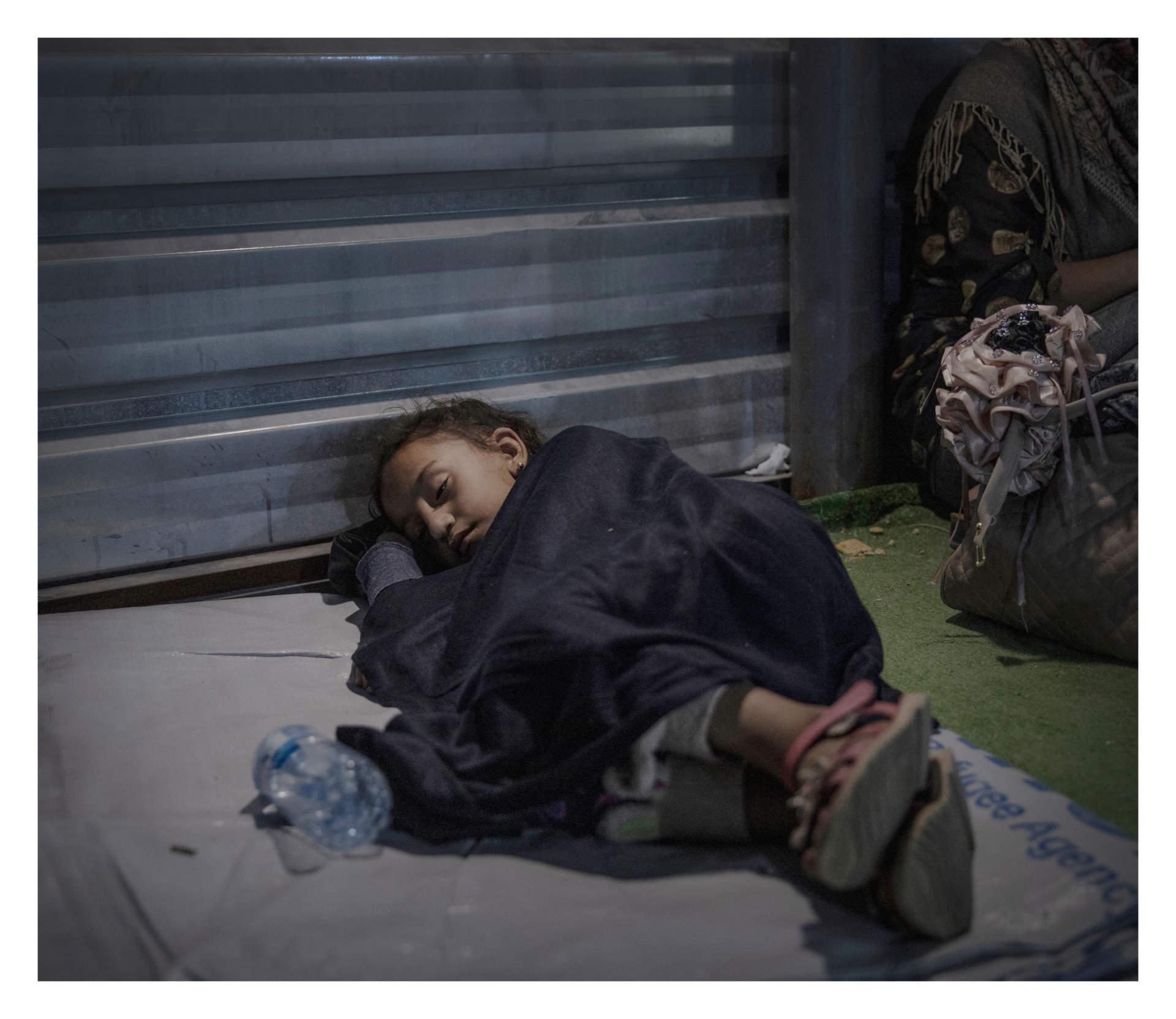 Fryad, 6 år.  BARDARASH, IRAKISKA KURDISTAN. Fryad och hennes familj tvingades fly från staden Amuda i norra Syrien näa den Turkiska gränsen. Nu sover hon på en vit presenning på golvet utanför flyktinglägret Bardarash i Irakiska Kurdistan. Bredvid henne står en ryggsäck och en mindre resväska med de tillhörigheter som familjen lyckats få med sig. Tillsammans med hundratals andra väntar de på ett tält att få övernatta i. Lägret kom till 2013 i massflykten undan IS, men sedan terroristerna besegrades har det varit övergivet. Tills nu. Familjen vet inte om och när de kan återvända hem igen.